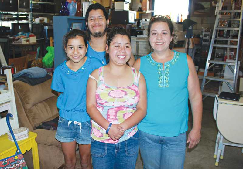 by: SUSAN MATHENY/THE PIONEER - At work in the Madras Habitat Restore are Geraldine, 12, Gabriel, 21, and Esperanza Hernandex, 13, with their mom Candida DeSosa.