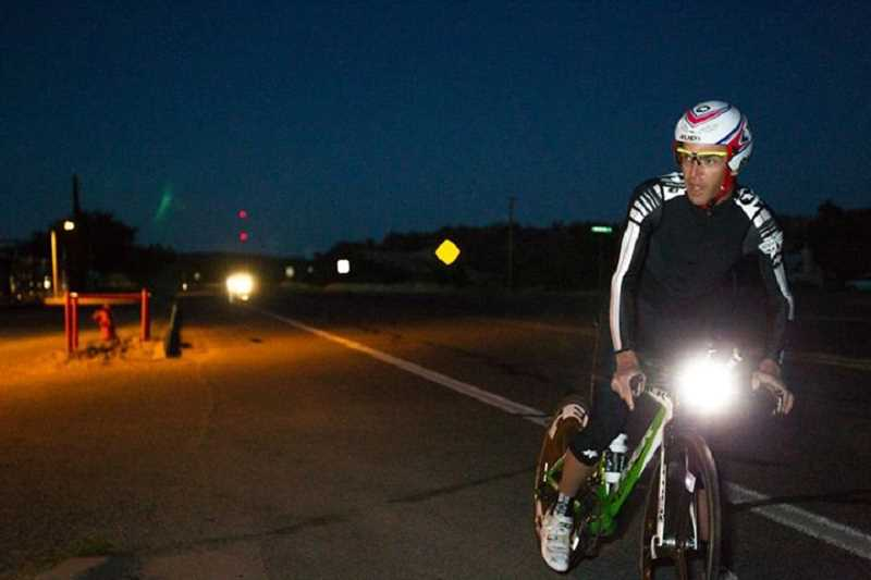 by: CRAIG BINGHAM - Puskas shines during a night transition on his bike race across the nation.