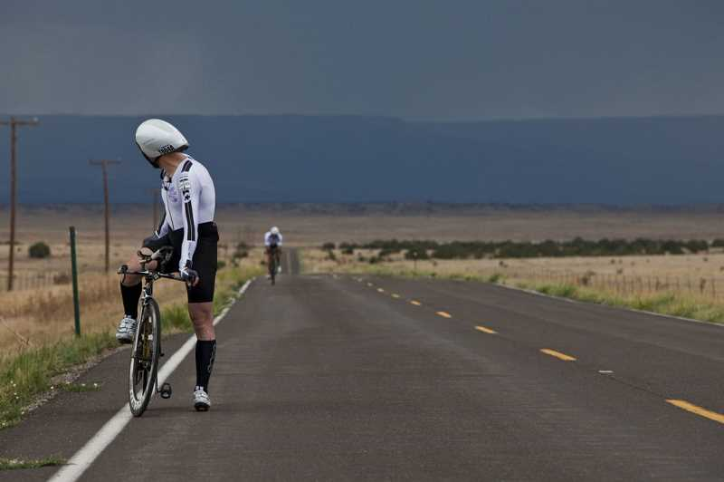 by: CRAIG BINGHAM - A rider looks back at a storm during the Race Across America.