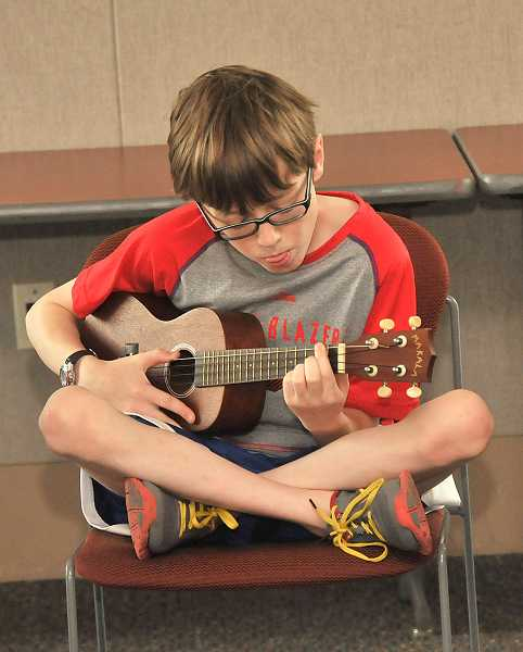 by: TIDINGS PHOTO: VERN UYETAKE - Elijah Cirioli concentrates while trying to learn some new chords.