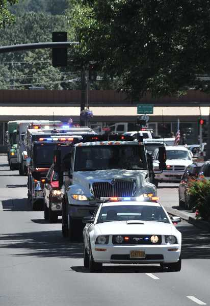 by: VERN UYETAKE - A procession involving dozens of emergency vehicles drove up A Avenue in Lake Oswego to reach the fire station where John J. Percins ashes will be on vigil until his service on Friday.