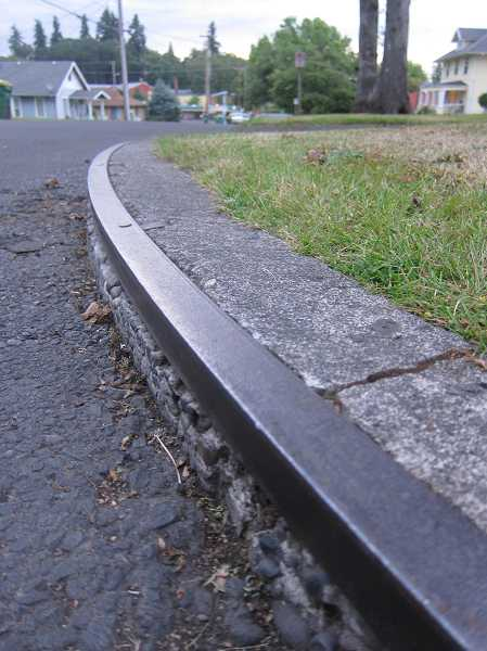 by: NEWS-TIMES PHOTO: KATHLEEN ROHDE - The street builders of 100 years ago lined certain curbs with metal to protect them from the buggy wheels that crashed against them.