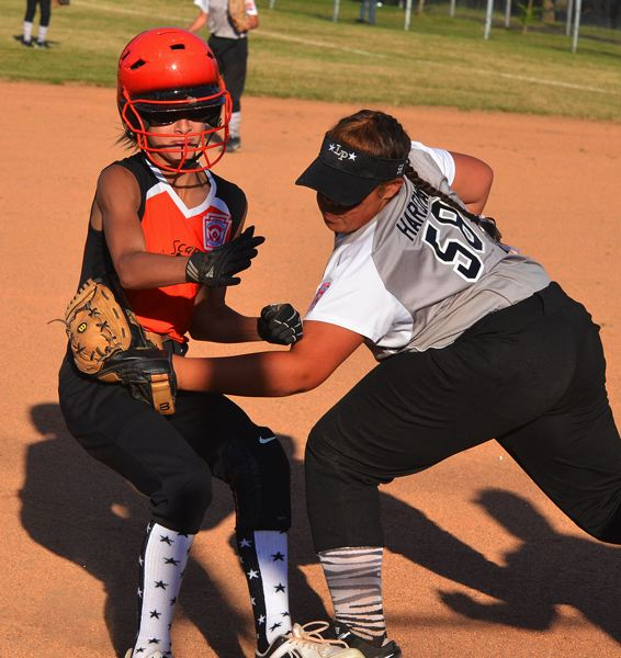 by: JOHN BREWINGTON - Erin Reardon of the Scappoose All-Stars softball team was out, but safe on this play. She had been obstructed earlier at second base. Scappoose lost the game.