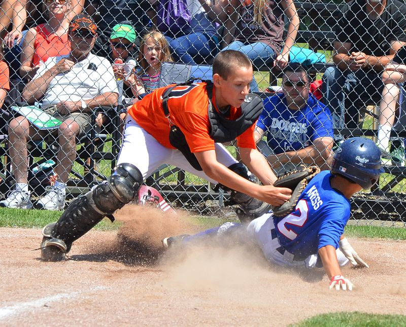 by: JOHN BREWINGTON - Scappoose's Gavin Larson tags out Paul Cress of Wilshire-Riverside during All-Star game on Sunday. Scappoose lost the game but was still in the tournament going into Thursday's game.