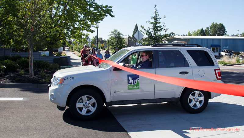 Tigard Mayor John L. Cook performs a drive-by ribbon cutting as he parks the first car in a new parking lot at the corner of Burnham Street and Main Street. The parking lot is the first in several construction projects planned for the street over the next two years.