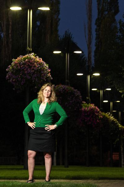 by: TIMES PHOTO: JAIME VALDEZ - Cindy Dolezel, sustainability manager with the city of Beaverton, stands near the LED street lights in front of the Beaverton City Library that she championed to be installed. In her previous career, Dolezel was a diplomatic courier for the U.S. State Department, taking on a mission to establlish embassies in Russia in the early 1990s.