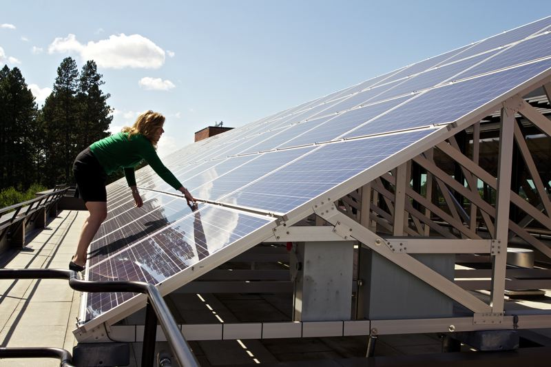 by: TIMES PHOTO: JAIME VALDEZ - Cindy Dolezel, sustainability manager with the city of Beaverton, scales the solar panel array atop the  Beaverton City Library that she worked to get installed. The former U.S. Army soldier uses her military experience and interrogation training to turn sustainable concepts into reality.