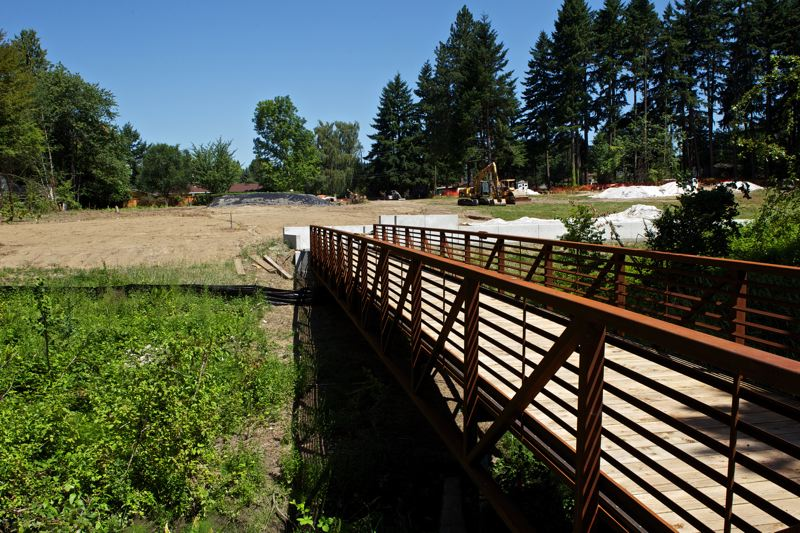 by: TIMES PHOTO: JAIME VALDEZ - Construction crews move dirt near the new footbridge at the Tualatin Hills Park and Recreation District's A.M. Kennedy Park to connect the park and its new sports field to Southwest Laurel Street, where a local business will allow park parking on evenings and weekends. The 2008 $100 million bond-funded project is one of many park district construction projects planned for this summer.