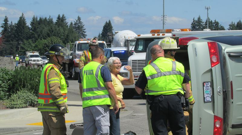 by: SPOTLIGHT PHOTO: MARK MILLER -  Scappoose resident Valerie Parks smiles in relief after emergency responders pulled her from Judy Thompsons overturned Toyota Sienna on Thursday, July 11. The minivan overturned after being involved in a two-vehicle crash at the intersection of Highway 30 and S.W. Havlik Drive in south Scappoose. There were no major injuries reported. The car can be fixed, said Thompson, who was helped out of the vehicle after Parks. Its the people that matter.