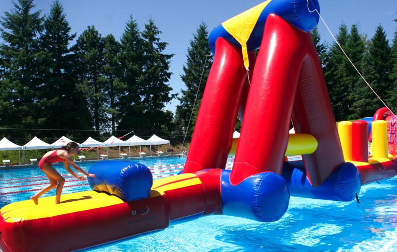 by: OUTLOOK PHOTO: JIM CLARK - The new pool toys at Mt. Hood Community Colleges Aquatic Center include an inflatable obstacle course.