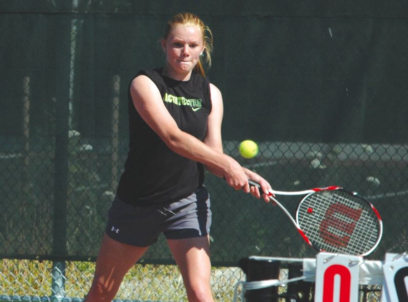 by: SANDY POST: PARKER LEE - Sandys McKenna Wells hits a backhand return during her win in the 14U championship match.