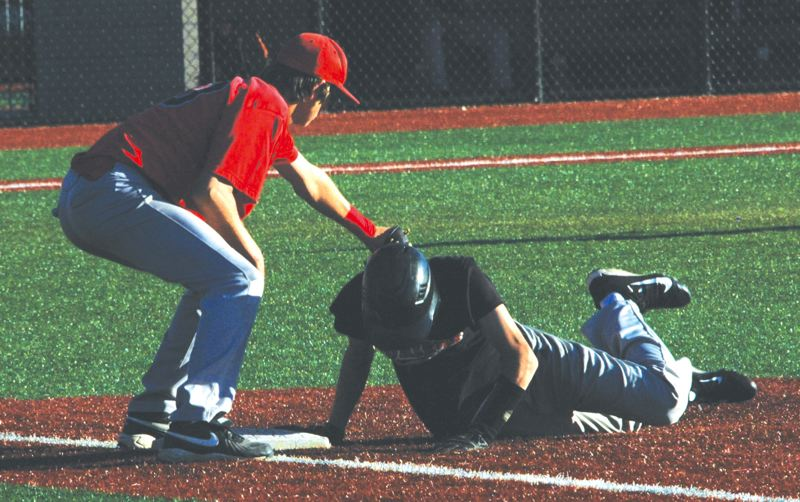 by: SANDY POST: PARKER LEE - Sandys Nick Martin dives back to first base safely after a pick-off attempt.
