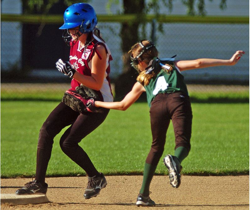 by: DAN BROOD - DOUBLE TIME -- Tualatin City's Olivia Ashley (left) gets to second base, for a double, before Tigard shortstop Kaitlyn Gearin can make the tag in Monday's district semifinal game. Tigard won 8-6.