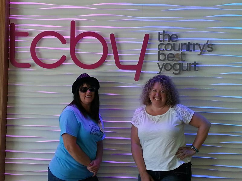 by: CONTRIBUTED PHOTO - Practicing their role as cash mobsters are two chamber members in front of the TCBY store, 16605 362nd Drive in Sandy — the site of a real cash mob that begins at 4 p.m. Saturday. Pictured are Debbie Grimes, left, and Lacy Renard.