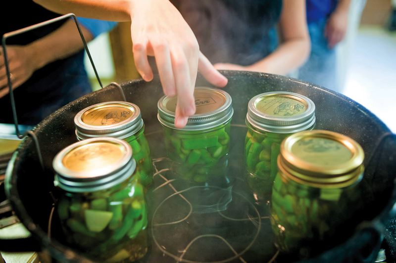 by: STAFF PHOTO - Students prepare asparagus for pickling. Properly sterilizing and sealing the jars can be the trickiest part.