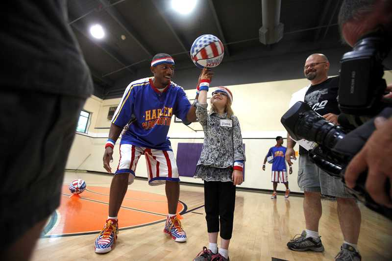 by: TIMES PHOTO: JONATHAN HOUSE - Alexus Osborn spins a basketball on her finger with a little help from Harlem Globetrotter 'Buckets' Blakes during a summer skills course at the Murray-Scholls 24-Hour Fitness. Osborn was recognized as a Junior Phenom for helping to save her family during a house fire last April.