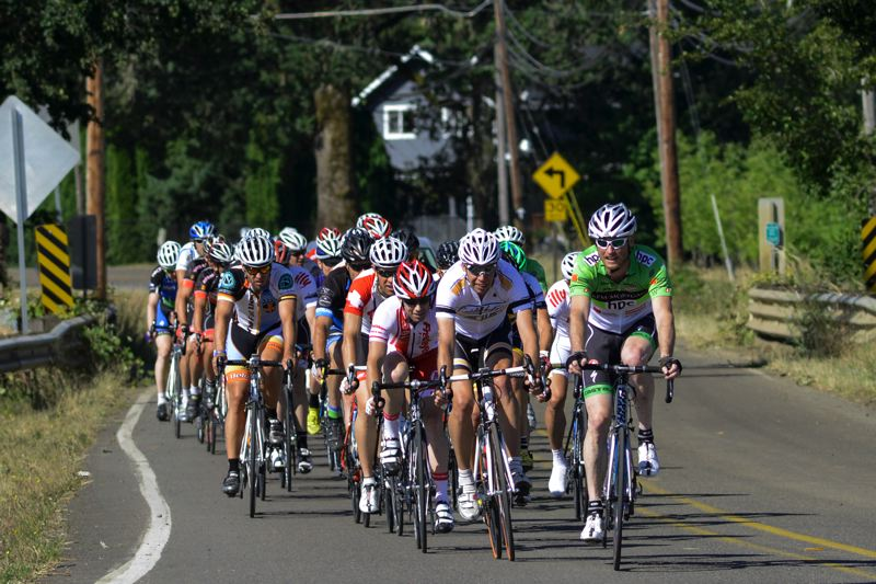 by: NEWS-TIMES PHOTO: CHASE ALLGOOD - A pack of riders heads into a turn on Sunday at the Montinore Road Race, a cycling event staged on a 10-kilometer circuit course in the rolling hills and vineyards of rural Forest Grove.