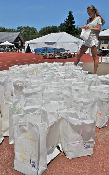by: J. BRIAN MONIHAN - National Charity League volunteer Elle Mayer prepares to place decorated luminaries around the Lake Oswego High School track. The bags contained candles set in sand and were lit at dark in a special ceremony to honor those with cancer.