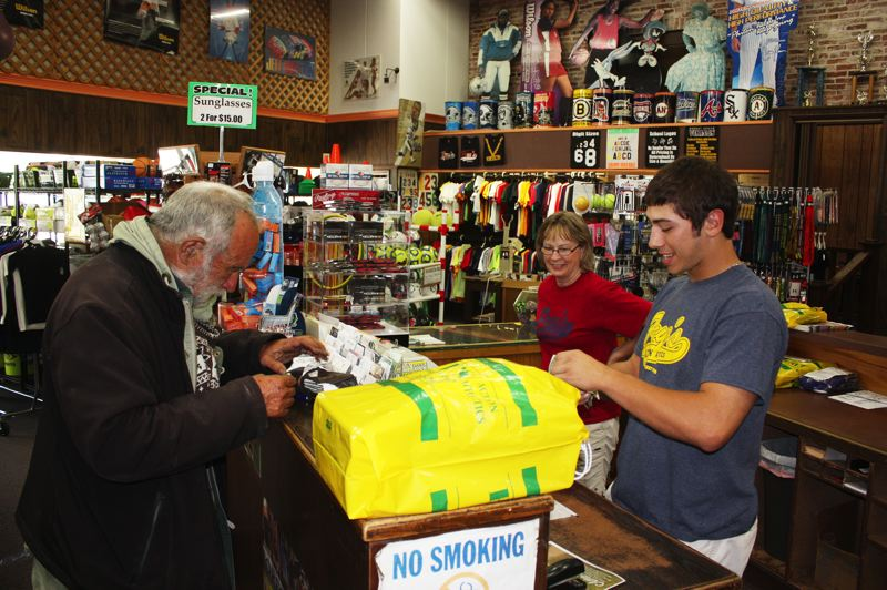 by: NEWS-TIMES PHOTO: DOUG BURKHARDT - 'I do a lot of walking,' says John, who stopped in to buy new shoes at Fryes Action Athletics on Pacific Avenue. Kyle Vanderkin and store manager Marine McBeth help him find the right pair.