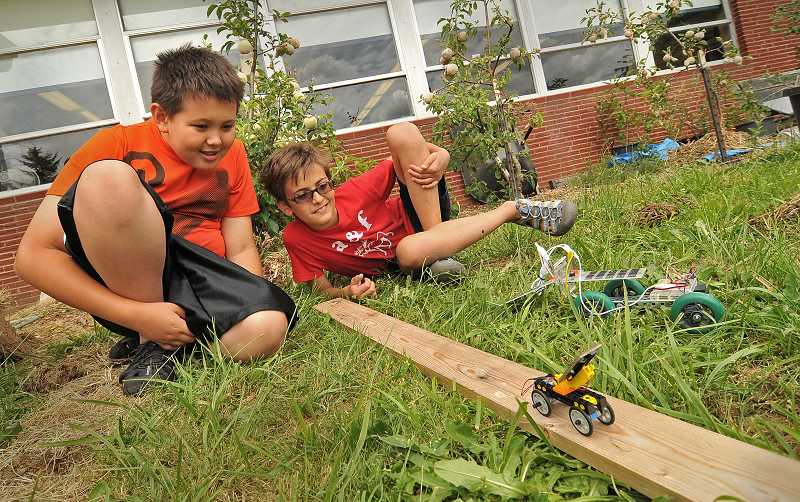 by: REVIEW PHOTO: VERN UYETAKE - Sixth-graders Alex Moreau, left, and Alex Alberte try out a scale model of their solar-powered car.