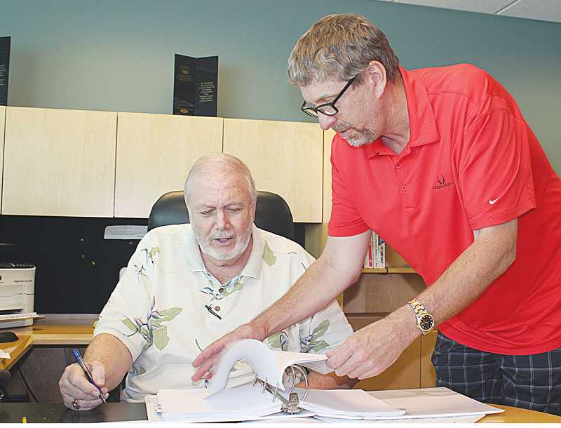 by: HOLLY M. GILL - Terry Hanlon, left, and Matt Thomas sign paperwork July 11 for the sale/purchase of Miller Ford.