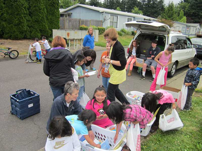 by: TIMES PHOTO: BARBARA SHERMAN - Diane Bonica (center), a longtime kindergarten teacher at Deer Creek Elementary, coordinates Deer Creek on Wheels, a program that for four years has provided free books to children every summer in several residential complexes, including Mountain View Estates.