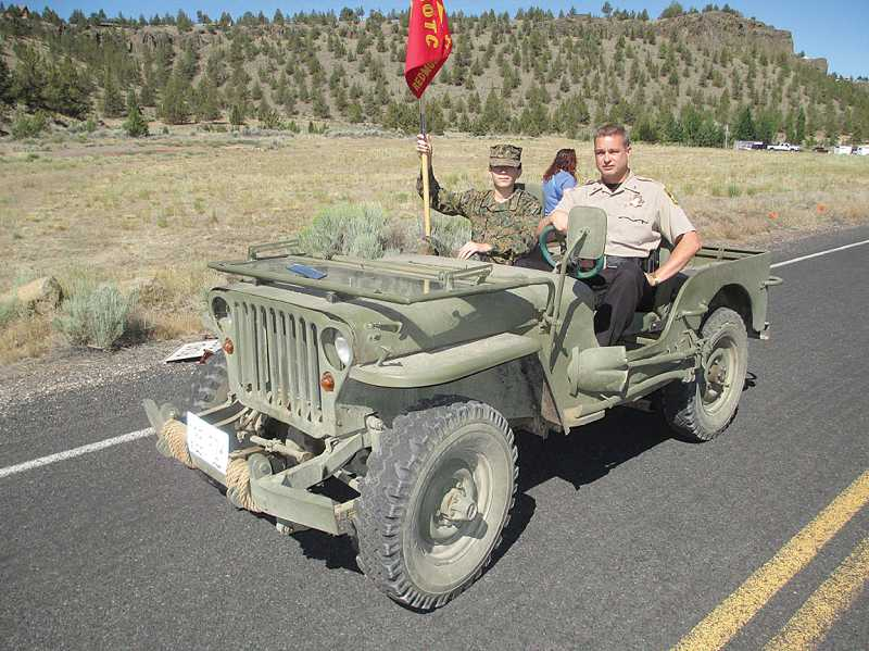 by: PHOTO BY JOHN BOWLER - Sheriff Jim Adkins rides in a Redmond JROTC Jeep in the Crooked River Ranch parade July 6.