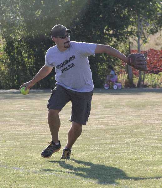 by: LINDSAY KEEFER - Zach Williams fields the ball for the Woodburn Police Department at July 11's police-versus-fire softball game at Centennial Park.
