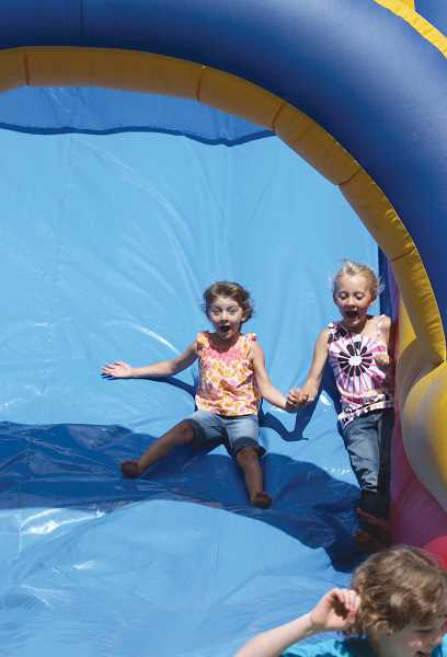 by: WOODBURN INDEPENDENT - From 11 a.m. to 4 p.m., children can take advantage of the kids zone  bouncy castle, as these girls did last year. The kids area will also include organized games at 1 p.m.