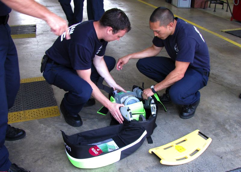 by: OUTLOOK PHOTO: MARA STINE - Firefighter/paramedics Greg Renfro and Andrew Nguyen set up a new machine that performs CPR on patients.