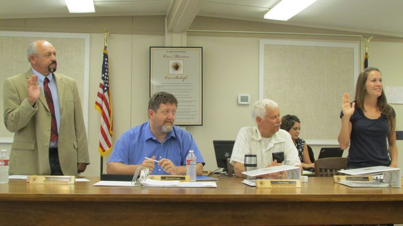 by: MARK MILLER - New school board members Gordon Jarman, far left, and Kellie Smith, far right, recite the oath of office as incumbents Marshall Porter, seated left, and Ray Biggs, seated right, look on. The third new board member, Jeff Howell, arrived late to the meeting and was sworn in separately.