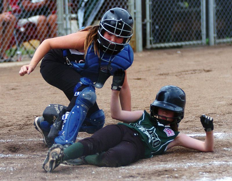 by: DAN BROOD - SHE'S SAFE -- Tigard's Kaitlyn Gearin (right) slides past the tag of Lents catcher Ellie Greene in Tuesday's Oregon State Tournament third-place game. Tigard won 13-5.