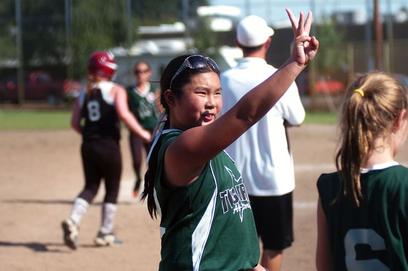 by: DAN BROOD - WE'RE NO. 3 -- Tigard's Kaylee Mo holds three fingers in the air following the team's win in the state tournament third-place game.