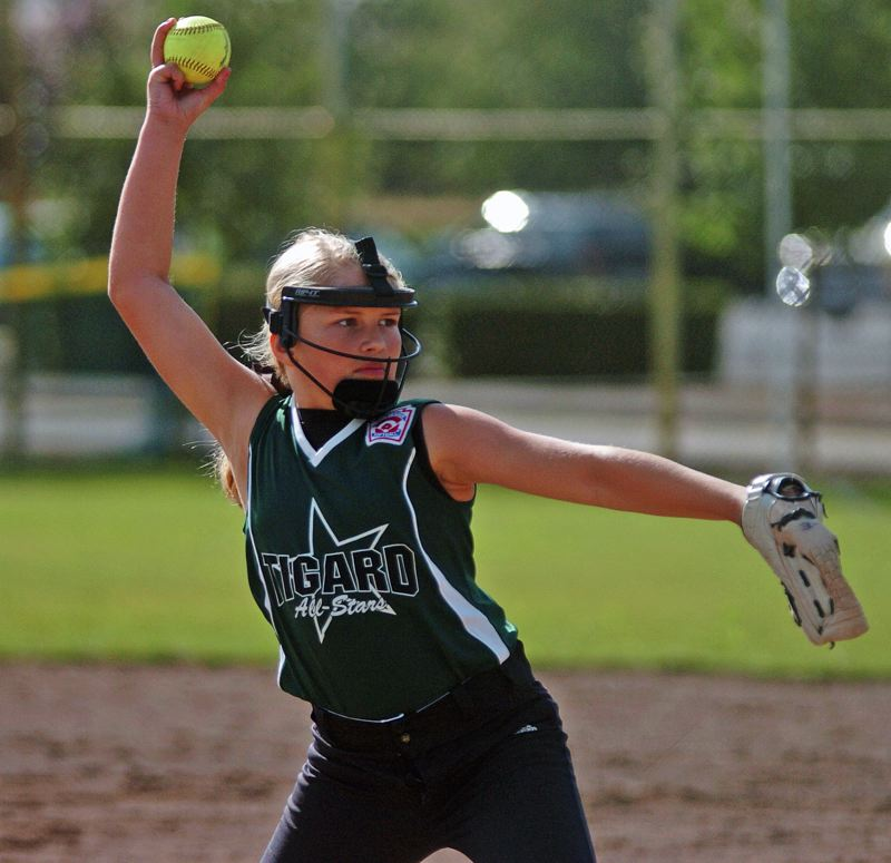 by: DAN BROOD - BRING THE HEAT -- Tigard's Taylor Corcoran gets ready to unleash a pitch during the win over Hood River.