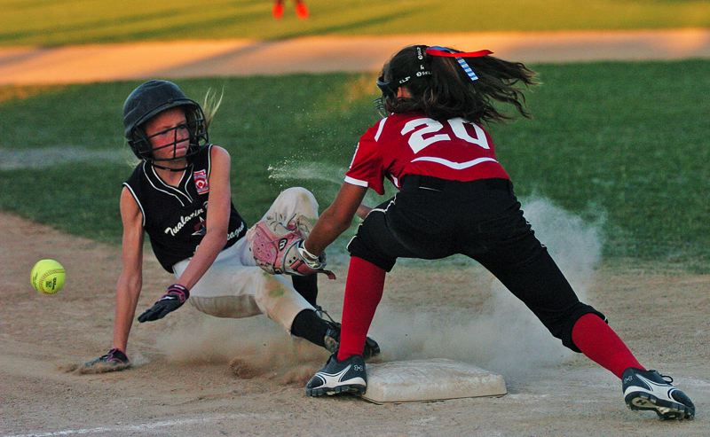 by: DAN BROOD - A CLOUD OF DUST -- Tualatin City's Camille Hall (left) slides safely to third base as Willow Creek's Raegan Kirsop reaches for the ball in Monday's game at the District 4 Tournament.
