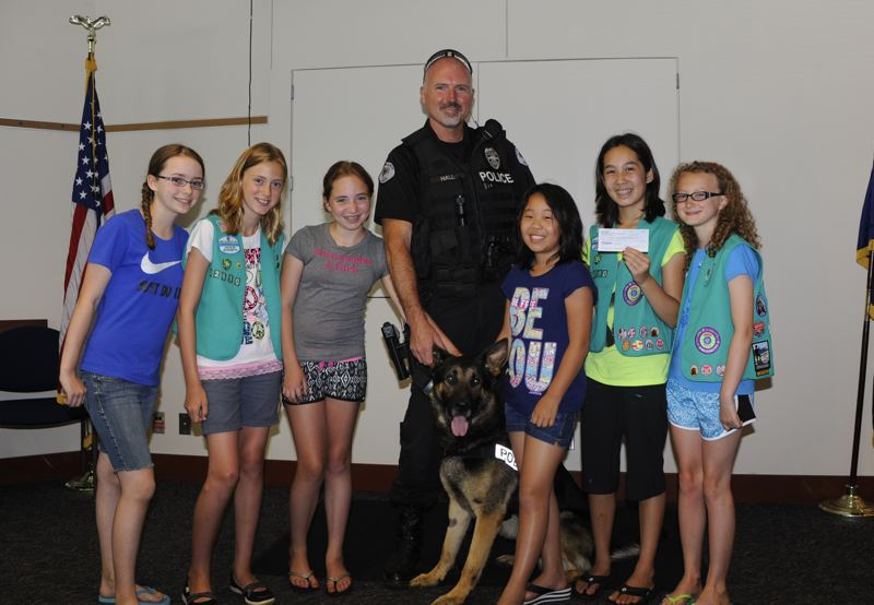 by: PHOTO COURTESY: GIRL SCOUT TROOP 42610 - Presenting Milwaukie Officer Les Hall and Yago with $100 collected from bottles and cans in North Clackamas neighborhoods are, from left, Emily Zak, Anna Hermens, Hannah Wilhelms, Valerie Tomita, Hannah Adsitt and Lindsey Gotter. Not pictured, but who also helped: Reese McDowell and Emily Gotter.