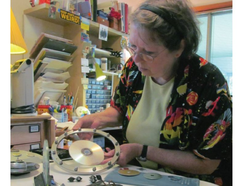 by: PHOTO BY ELLEN SPITALERI - Deborah Ellis gets ready for Cracked Pots, working on a clock made with a light fixture and CD base.