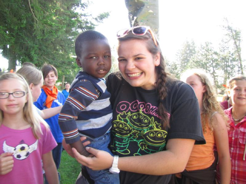 by: SUBMITTED PHOTO - Rex Putnam High School graduate Tiffany Johnson meets the son of a Sudanese refugee at a church camp where she made the decision to work at an Ivory Coast center for children who have mental and physical disabilities.
