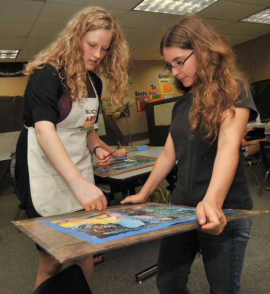 by: PAMPLIN MEDIA GROUP: VERN UYETAKE - MacKenzie Weber receives instruction from Amber Sprague on her collage.