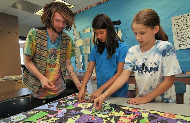 by: PAMPLIN MEDIA GROUP: VERN UYETAKE - From left, Dillon Silva instructs Julia Winkle and Maura Schramm on their cut-paper collage mural.