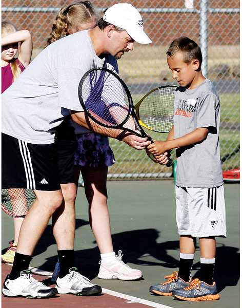 by: PHOTO BY JO WHEAT - Lance Berkey instructs Cal Waite on the proper grip to use when handling a tennis racket.