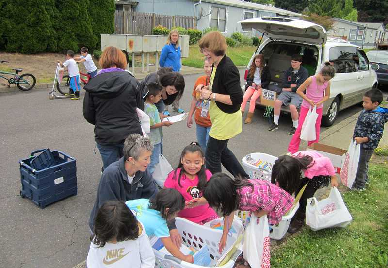 by: BARBARA SHERMAN - CHRISTMAS IN JUNE - Deer Creek kindergarten teacher Diane Bonica (center) helps kids at Mountain View Estates choose books during Deer Creek on Wheels' first stop there of the summer.