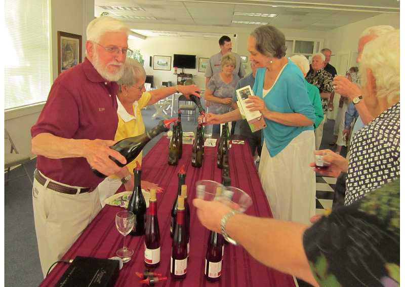 by: BARBARA SHERMAN - SAMPLING THE BEST - Ron Vuylsteke and his wife Pam pour samples of Oak Knoll wines during a tasting July 14 at the Highlands Clubhouse following the showing of an OPB special and his talk about Oregon's wine industry.