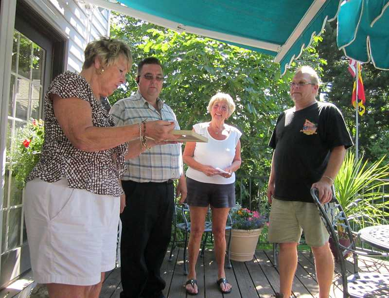 by: BARBARA SHERMAN - ALMOST TWINS TIMES TWO -- Looking at an old family photo are Jan Law (left) and Alice Furey, who were born 15 months apart; also on the patio are Jan's son Alex (left) and Alice's son Eric, who were born three days apart.