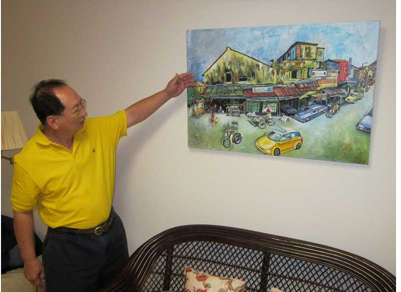 by: BARBARA SHERMAN - GROWING ARTWORK PORTFOLIO - Prolific artist Paul Tee points to a painting he did that hangs in his Bull Mountain home; he likes to paint scenes from old Asia both from memory and photos.