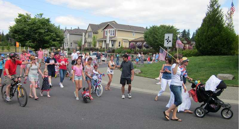 by: BARBARA SHERMAN - PATRIOTIC NEIGHBORHOOD - Parade participants of all ages kick off the Edgewater on the Tualatin's Fourth of July parade with a loop around the roundabout.