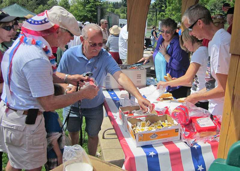 by: BARBARA SHERMAN - BEST DAY EVER! - In the King City Community Park gazebo, volunteers hand out hot dogs to hungry parade participants.