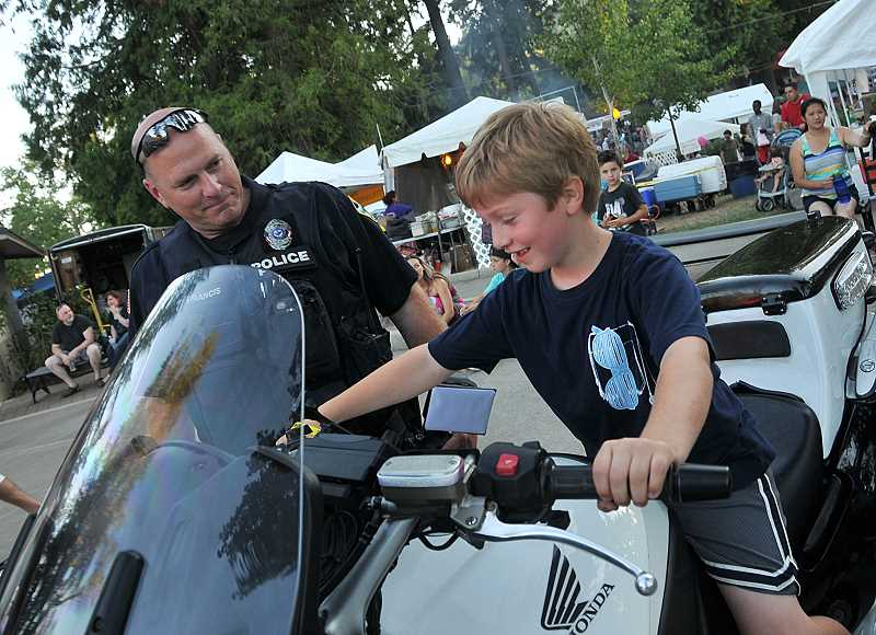 by: VERN UYETAKE - A boy tests out a police motorcycle during the fair.