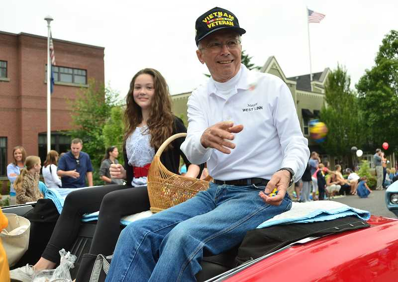 by: VERN UYETAKE - Mayor John Kovash tosses candy to parade-goers Saturday morning.