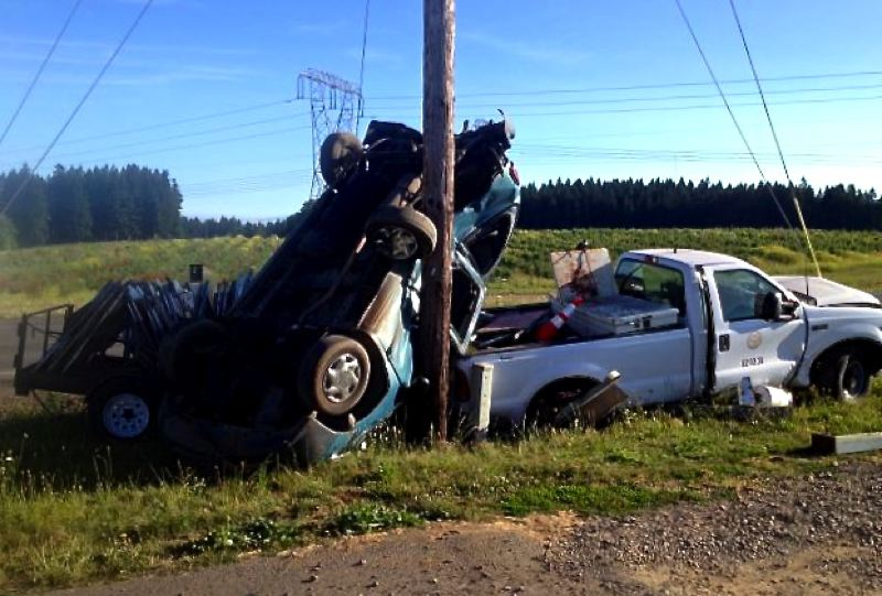 by: CONTRIBUTED PHOTO: OREGON STATE POLICE - After impact, both vehicles ended up on the east side of Highway 211 with the van on its top resting against the back of the county pickup, trailer and a power pole.